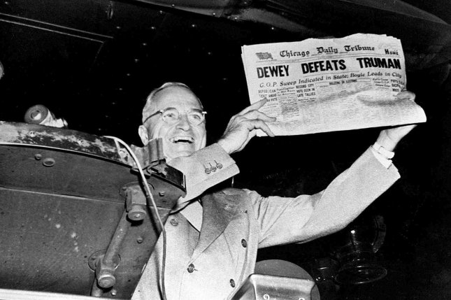 "President-elect Harry S. Truman laughs heartily as he holds an early edition of the Chicago Tribune for November 4, 1948, with the headline ""Dewey Defeats Truman."" The newspaper, whose headline jumped to an erroneous conclusion as early election returns came in, was shown to Truman as he stopped in St. Louis, Missouri, during his victorious return trip to Washington, D.C. File photo UPI."