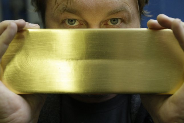 A worker holds a 13 kilogram (28.66 pound) gold bar at a foundry in Magadan, about 6,000 kilometers (3,700 miles) east of Moscow. FILE/UPI/Anatoli Zhdanov