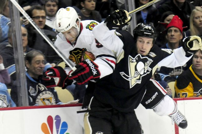 Pittsburgh Penguins Brooks Orpik checks and lifts Chicago Blackhawks Steve Montador off the ice and into the glass in the first period at Consol Energy Center in Pittsburgh, Pennsylvania on December 20, 2011. UPI/Archie Carpenter