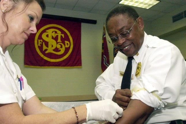 St. Louis Fire Commissioner and Chief Sherman George rolls his sleeve up for paramedic Donna Lowe as she performs a hepatitis C test on Sept. 9, 2002. It was the first fire department in the U.S. to test all firefighters and paramedics for the blood-borne virus that is transmitted by direct exposure to contaminated blood. Photo by Bill Greenblatt/UPI