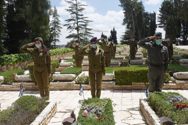 Israeli soldiers wear masks for protection against the coronavirus while saluting the graves of fallen soldiers. Photo by Debbie Hill/UPI