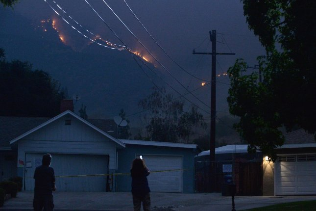 Flames from the Bobcat Fire appear above homes in the foothills of Monrovia, Calif. on Friday. Photo by Jim Ruymen/UPI