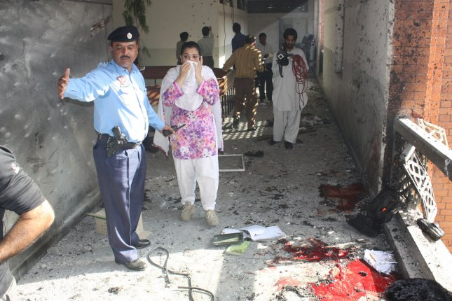 Members of a bomb disposal team survey damage at the site of two suicide bomb blasts, which killed 4 students and wounded at least 18 people, at the International Islamic University, in Islamabad, Pakistan on October 20, 2009. UPI/Sajjad Ali Qureshi