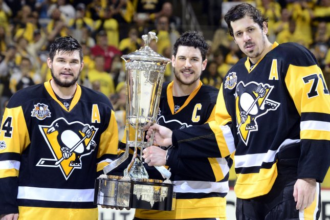 Pittsburgh Penguins left wing Chris Kunitz (14) (L) joins Pittsburgh Penguins center Sidney Crosby (87) (center) and Pittsburgh Penguins center Evgeni Malkin (71) as they pose with the Prince of Wales Trophy after the 3-2 double overtime victory against the Ottawa Senators of game seven to win the Eastern Conference Finals of the Stanley Cup Playoffs at PPG Paints Arena in Pittsburgh on May 25, 2017. File photo by Archie Carpenter/UPI