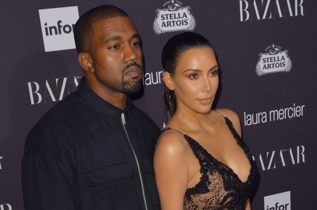 Kanye West (L) poses with his wife Kim Kardashian. The couple's son Saint West was seen dancing with Chance the Rapper's daughter Kensli. File Photo by Andrea Hanks/UPI