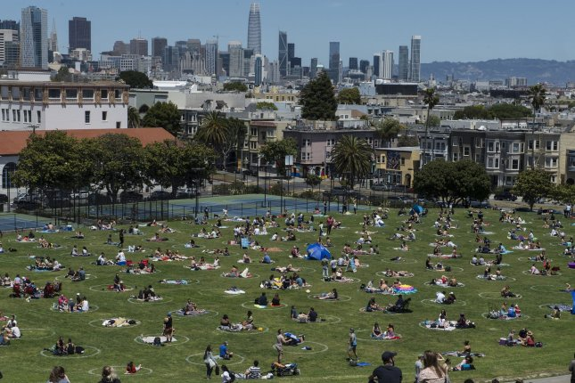 Groups hang out in pre-drawn circles in Delores Park in San Francisco on Saturday. Warm weather and a holiday weekend brought out thousands to practice their own brands of social distancing. Photo by Terry Schmitt/UPI