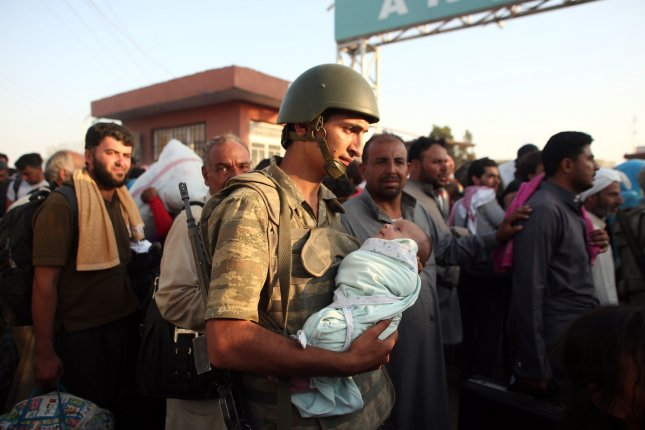 Turkish soldiers help Syrian families by carrying their babies while they are waiting with hundreds of refugees at the Syrian side of the border crossing in Akcakale, Sanliurfa province, south-eastern Turkey, June 14 2015. They are trying to cross to the Turkish side as they are fleeing from the fighting between the Kurdish People's Protection Units (YPG) military group and Islamic State (ISIS). Photo by Ebrahem Khadir/ UPI