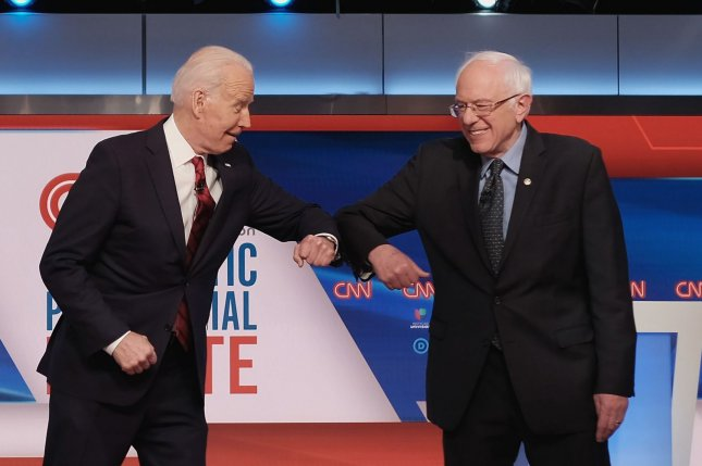 Democratic presidential candidates Joe Biden (L) and Bernie Sanders bump elbows before participating in a debate at a CNN studio in Washington, D.C. on March 15. Photo by CNN/UPI
