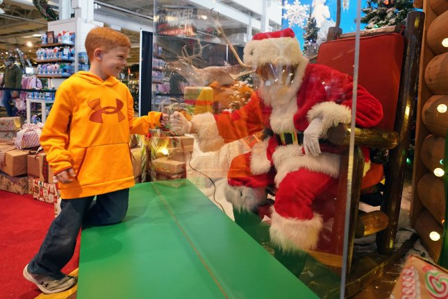 A child interacts with Santa Claus on Sunday through a sheet of plexiglas at the Bass Pro Shop in St. Charles, Mo, a suburb of St. Louis. Photo by Bill Greenblatt/UPI