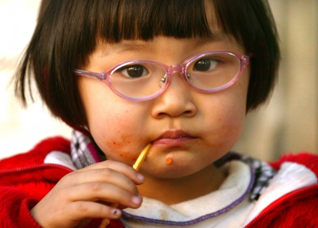 Added sugar in food, beverages may increase risk of heart disease. A young Chinese girl finishes her sugar coated fruit-on-a-stick outside her home in downtown Beijing. (UPI Photo/Stephen Shaver)