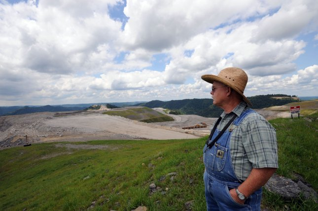Larry Gibson walks on his land on Kayford Mountain in southern West Virginia, which overlooks a mountains leveled by a strip mining practice called Mountain Top Removal, July 19, 2009. Gibson's family has lived on Kayford Mountain since the late 1700's, when their mountain was the lowest lying point in the area. In 1986 coal companies started blast-flattening the mountains to remove coal with mountain top removal. Today, Gibson's property is the highest point of land around and is enveloped by 12,000 acres of flattened mountains. Mountain top removal is the controversial mining technique that blasts off the tops of mountains so massive machines can mine the thin seams of coal. The mountain top debris is dumped into nearby valleys and streams, creating valley fills. More than 3,000,000 pounds of explosives are used against the West Virginia mountains every work day. Critics say the mining process damages the environment while supporters say the process provides flat land suitable for many uses. UPI Photo/Debbie Hill