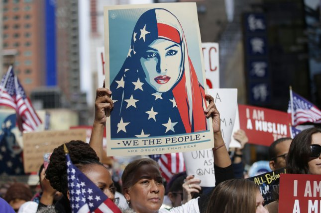 A sign with the face of a Muslim girl wearing an American flag as a hijab headdress was hoisted up by protesters at the Today I am a Muslim Too rally against the immigration policies of President Donald Trump in Times Square in New York City on Sunday. Photo by John Angelillo/UPI