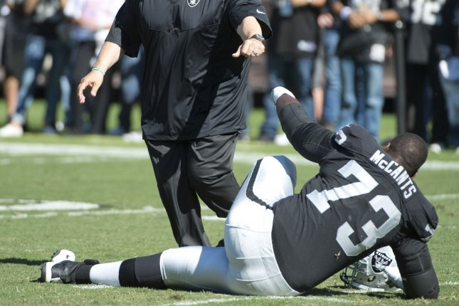 Ex-Oakland Raiders interim head coach Tony Sparano (L) bumps fists with former Raiders tackle Matt McCants (73) during warmups to play the Arizona Cardinals on October 19, 2014 at O.co Coliseum in Oakland, California. File photo by Terry Schmitt/UPI