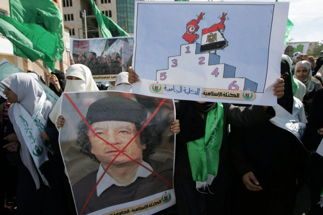 Palestinian students hold up the placards sduring a protest against Libyan leader Moammar Gadhafi in Gaza City on February 22, 2011. Gadhafi clung to control of his country as witnesses in Tripoli reported food shortages and violence by security forces. UPI/Ismael Mohamad