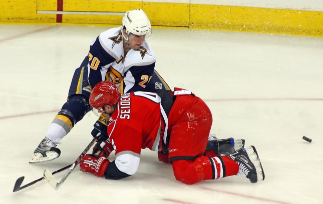 Carolina Hurricanes' Dennis Seidenberg (4) and Buffalo Sabres' Daniel Paille (20) battle for the puck during the first period of an NHL Hockey game in Raleigh, North Carolina, April 9, 2009. (UPI Photo/Karl DeBlaker)