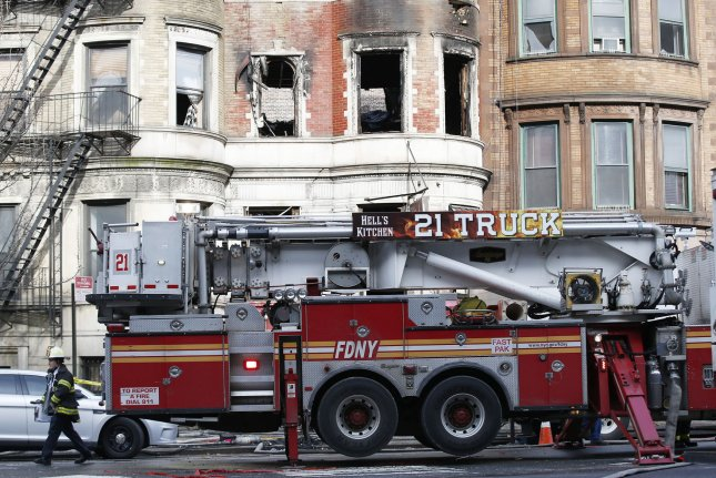 Firefighters work at the scene Friday of a five-alarm fire that broke out in the basement of 773 St. Nicholas Ave. in New York City. The building was being used as a filming location for a movie starring Bruce Willis. Photo by John Angelillo/UPI