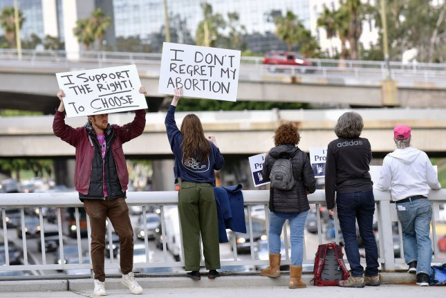 Abortion rights activists wave signs on the Wilshire overpass overlooking the 110 freeway at a Stop Abortion Bans rally organized by NARAL Pro-Choice California in Los Angeles on May 21. File Photo by Chris Chew/UPI