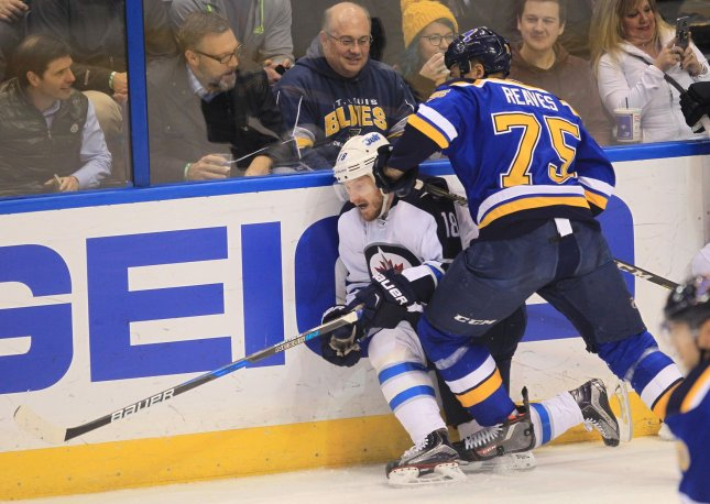 Bryan Little of the Winnipeg Jets is forced into the boards by the St. Louis Blues' Ryan Reaves during a game last season. Photo by Bill Greenblatt/UPI
