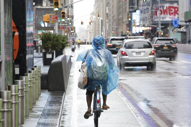 A cyclist wears a plastic rain covering while riding in Times Square as tropical storm Fay approaches New York City on July 10, 2020. A change in the weather pattern this week will not only bring wet weather into the Northeast, but also usher cooler air into the region. File Photo by John Angelillo/UPI
