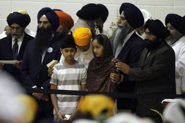 The 11-year-old son and 12-year-old daughter of shooting victim Prakash Singh are are comforted by mourners at a memorial service and visitation August 10, 2012, for six members of the Sikh temple mass murder at Oak Creek High School in Oak Creek, Wis. Wade Michael Page, a member of a racist neo-nazi group, has been identified as the lone gunman who killed six people, and then himself, during Sunday services at the Sikh Temple August 5. File Photo by Allen Fredrickson/UPI