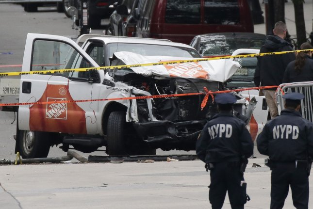 New York police watch Wednesday as workers collect evidence around a rented truck used to strike pedestrians in Lower Manhattan. Photo by John Angelillo/UPI