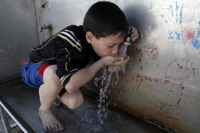 A child drinks water from a tap at the United Nations Relief and Works Agency in the Gaza Strip refugee camp. A U.N. report Monday warned that growing stresses on the planet could lead to severe water shortages by 2050. File Photo by Ismael Mohamad/UPI
