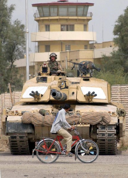 REX20030041101 - BASRA, Iraq, April (UPI) -- A Challenger 2 Tank from the Queen's Royal Lancers holds a position as a local biker rides by in Basra, Iraq, in April, 2003. rlw/REX FEATURES UPI.**Europe Out**
