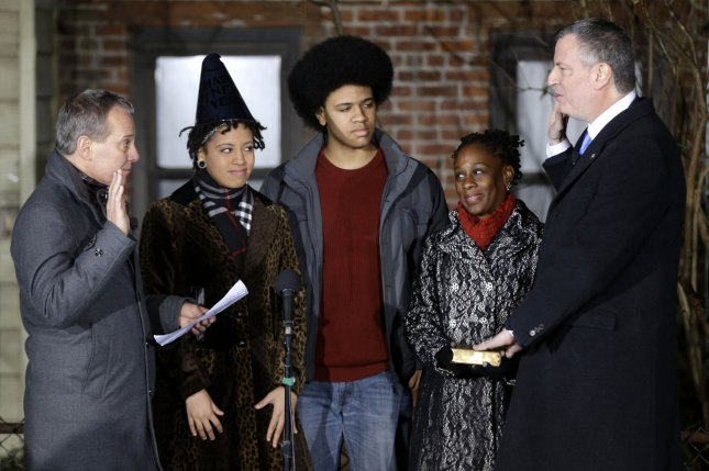 Bill de Blasio is sworn in as the mayor of New York City by State Attorney General Eric Schneiderman (L) while his family Chiara de Blasio (2nd,L) Dante de Blasio (C) and Chirlane McCray look on at the start of the new year, Wednesday, Jan. 1, 2014 in New York. De Blasio took the oath of office moments after midnight at his home in Park Slope, Brooklyn. His inauguration will be celebrated at noon Wednesday on the steps of City Hall when he takes the oath again, which will be administered by former President Bill Clinton. UPI/Seth Wenig/Pool