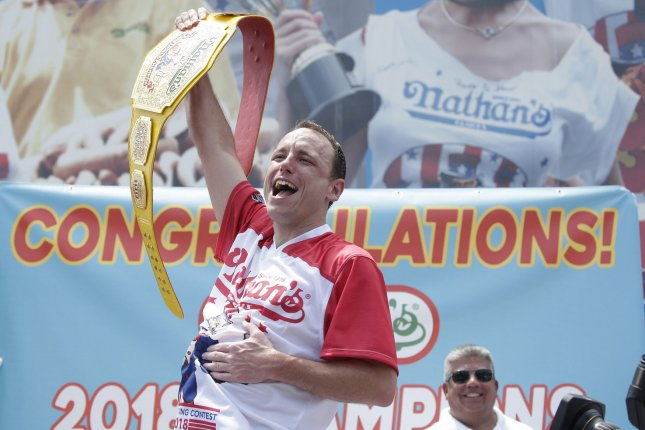 Joey Chestnut celebrates with a trophy and Championship Mustard Belt after his victory Wednesday at the 102nd Nathan's Famous Fourth of July International Hot Dog Eating Contest on Coney Island, N.Y. Photo by John Angelillo/UPI