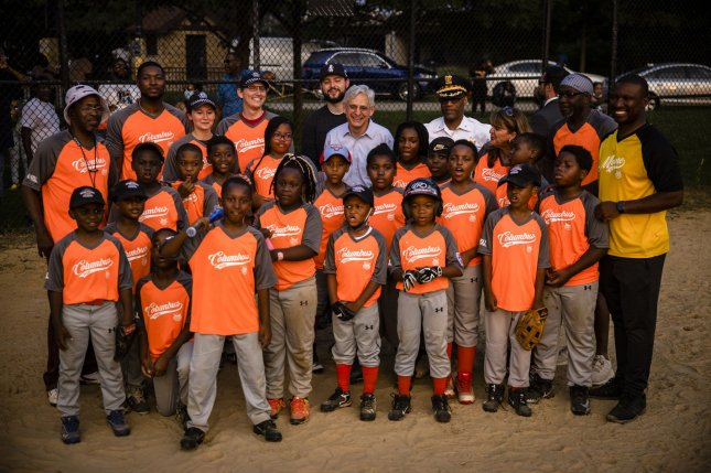 Merrick Garland, U.S. attorney general, poses for a photo with the children and coaches playing in a youth baseball game held by the Chicago Westside Sports on July 22. The next round of child tax credit payments will go out this week. File Photo by Samuel Corum/UPI