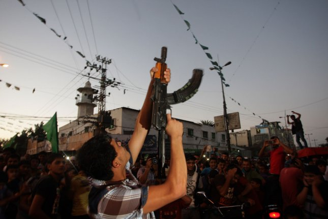 A Palestinian gunman fires in the air while celebrating after a deal had been reached between Hamas and Israel over a long-term end to seven weeks of fighting in the Gaza Strip on August 26, 2014 in Gaza City. Israel has agreed to observe an unlimited ceasefire in the Gaza Strip. UPI/Ismael Mohamad