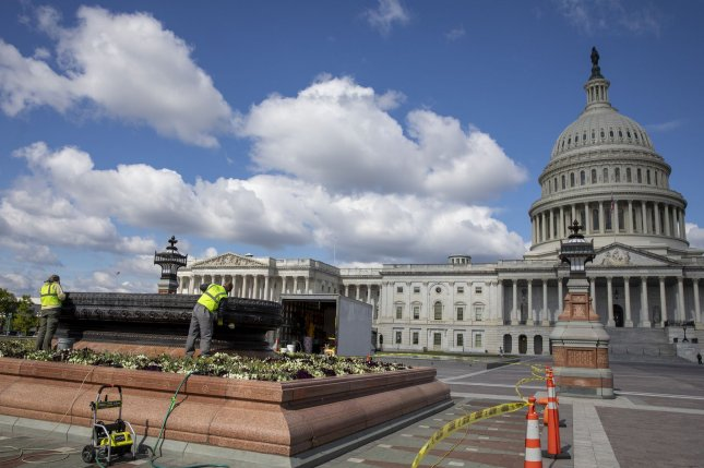A group of workers perform manual labor on a water fountain in front of the U.S. Capitol in Washington, D.C., on May 12. File Photo by Tasos Katopodis/UPI