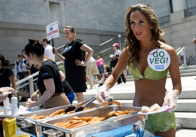 A PETA model hands out vegan hot dogs in front of the House Rayburn Office Building. UPI/Kevin Dietsch
