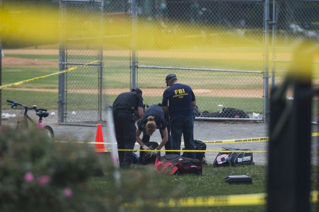 Investigators with the FBI evaluate items left at Simpson Field in Alexandria, Va., after a gunman started shooting at a Republican congressional baseball practice that was held Wednesday for an upcoming charity event. House Majority Whip Steve Scalise and three others were shot in the attack. Photo by Molly Riley/UPI