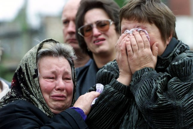 Relatives of more than 100 people who were killed in the September 13, 1999, bombing in an eight-story apartment building, cry at the site of explosion in Moscow on September 13, 2000. File Photo by Maxim Marmur/UPI