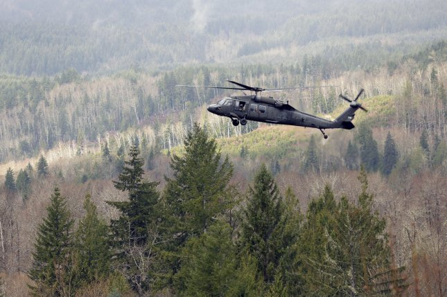 A military search and rescue helicopter hovers over the debris field on on March 27, 2014 in Oso, Washington. UPI/Ted Warren/Pool