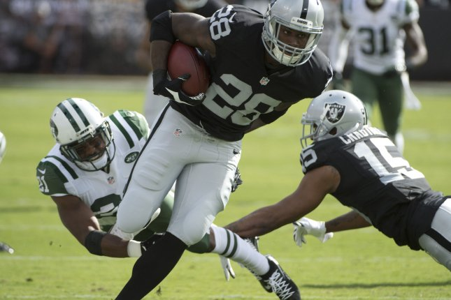 Former Oakland Raiders running back Latavius Murray (28) is tripped up by former New York Jets cornerback Marcus Gilchrist (21) on a 26-yard run in the first quarter at O.co Coliseum in Oakland, California on November 1, 2015. File photo by Terry Schmitt/UPI