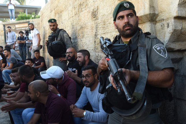An Israeli border police stands near Palestinians protesting outside the Damascus Gate of the Old City of Jerusalem on Tuesday in remembrance of the sixty Palestinian protesters killed by Israeli forces on the Gaza border yesterday. Photo by Debbie Hill/UPI