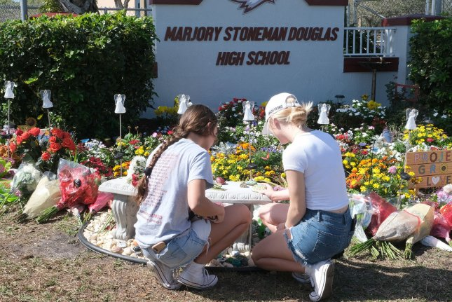 Students lay notes and flowers at a makeshift memorial at Marjory Stoneman Douglas High School in Parkland, Fla., after the April 14, 2018, attack. File Photo by Gary Rothstein/UPI