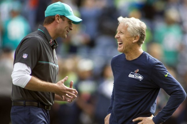 Seattle Seahawks coach Peter Carroll, right, talks to former Miami Dolphins head coach Adam Gase. File photo by Jim Bryant/UPI