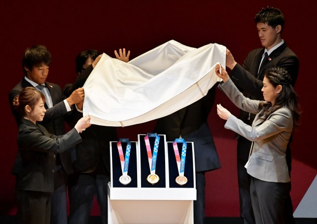 Olympic officials unveil the gold, silver and bronze medals Wednesday at the One Year to Go ceremony for the 2020 Summer Olympic games in Tokyo. Photo by Keizo Mori/UPI