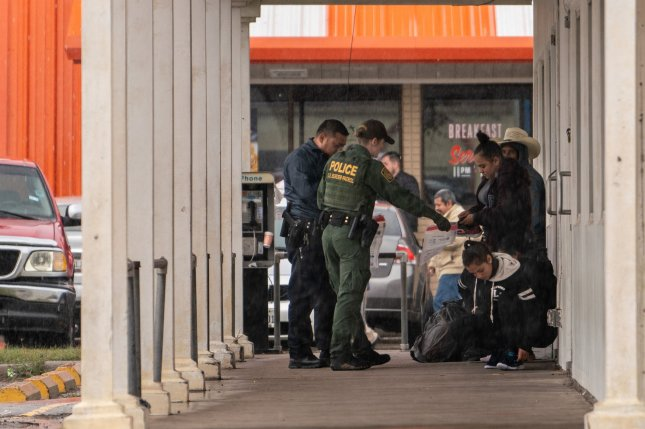 U.S. border patrol agents detain a group of immigrants 500 yards north of the Mexican border in Hidalgo, Texas, in January. The Justice Department Monday asked the Supreme Court to allow its new rule to go into effect nationwide forcing immigrants to file for asylum in the country they crossed into before reaching the U.S. Photo by Ken Cedeno/UPI