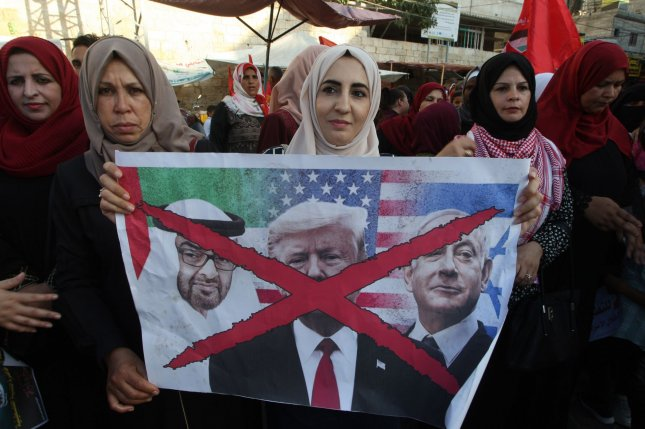 A Palestinian demonstrator holds a banner depicting U.S. President Donald Trump, Israeli Prime Minister Benjamin Netanyahu and UAE Crown Prince Sheikh Mohammed bin Zayed al-Nahyan during a rally in southern Gaza on August 18, to oppose a U.S.-brokered diplomatic agreement between Israel and the United Arab Emirates. File Photo by Ismael Mohamad/UPI