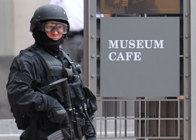 A S.W.A.T. police officer stands outside of an entrance for the U.S. Holocaust Memorial Museum after a man open fired on security guards inside the museum, in Washington on June 10, 2009. The gunman and a wounded security guard have been transported to George Washington University Hospital for treatment. (UPI Photo/Kevin Dietsch)