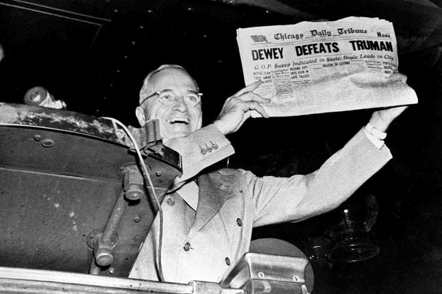 """President-elect Harry S. Truman laughs heartily as he holds an early edition of the Chicago Tribune for November 4, 1948, with the headline """"Dewey Defeats Truman."""" The newspaper, whose headline jumped to an erroneous conclusion as early election returns came in, was shown to Truman as he stopped in St. Louis, Missouri, during his victorious return trip to Washington, D.C. Photo by Frank Cancellare/UPI"""