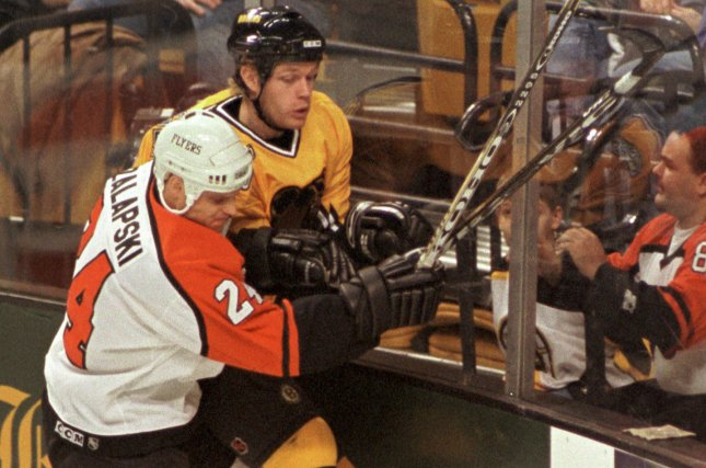 Former Philadelphia Flyers defenseman Zarley Zalapski, front, knocks Boston Bruins' Ken Belanger into the boards while the two were chasing after the puck. File photo by Lee K. Marriner/UPI