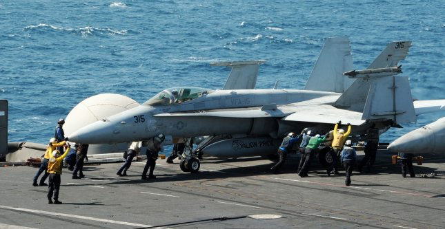 Sailors guide an F/A-18C Hornet on the flight deck of the aircraft carrier USS George HW Bush (CVN 77) of the U.S. 5th Fleet in the Persian Gulf on August 7, 2014. Two F/A-18 jets from the USS George HW Bush dropped 500-pound bombs on ISIS militants advancing on the Kurdish capital of Irbil, Iraq. UPI/Lorelei Vander Griend/US NAvy