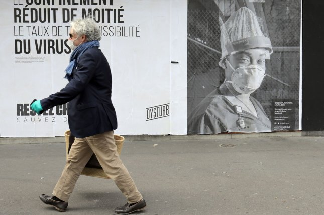 A man passes a poster that warns of the risks of the coronavirus disease on a street in Paris, France, on April 28. Photo by Eco Clement/UPI