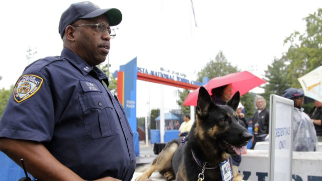 A NYPD police officer and police dog stand guard at the entrance at the U.S. Open Tennis Championships in a 2011 file photo. UPI/John Angelillo