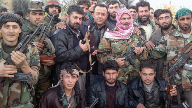 Opposition Syrian Free Army members hold their guns as they attend a protest against Syria's President Bashar al-Assad in Jrjanaz near Idlib in Syria on February 11, 2012. UPI